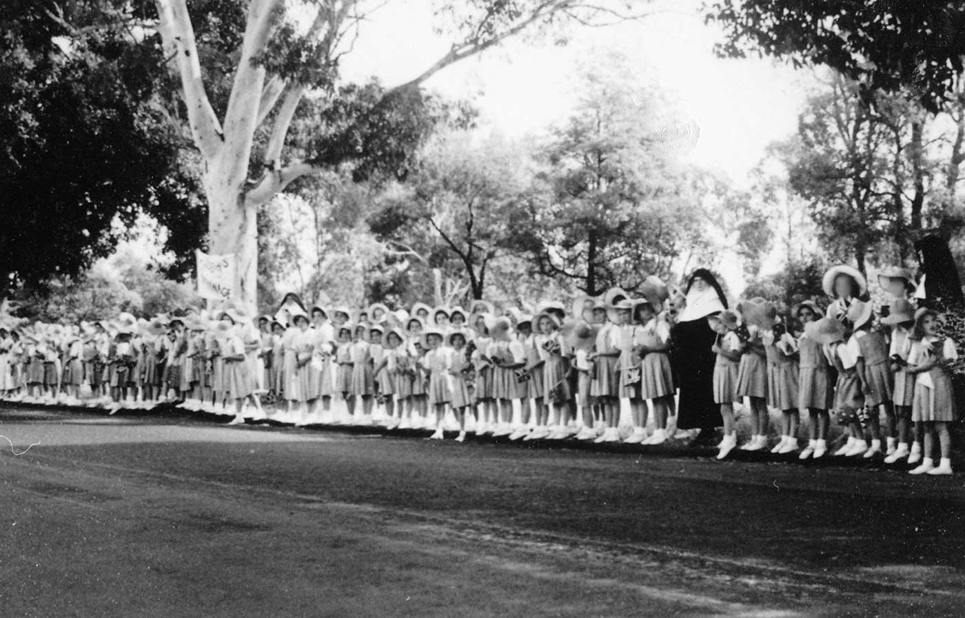 Black and white image showing a long line of girls in uniform, standing at the side of a street. There are three nuns with with girls. Various trees form a backdrop. - click to view larger image