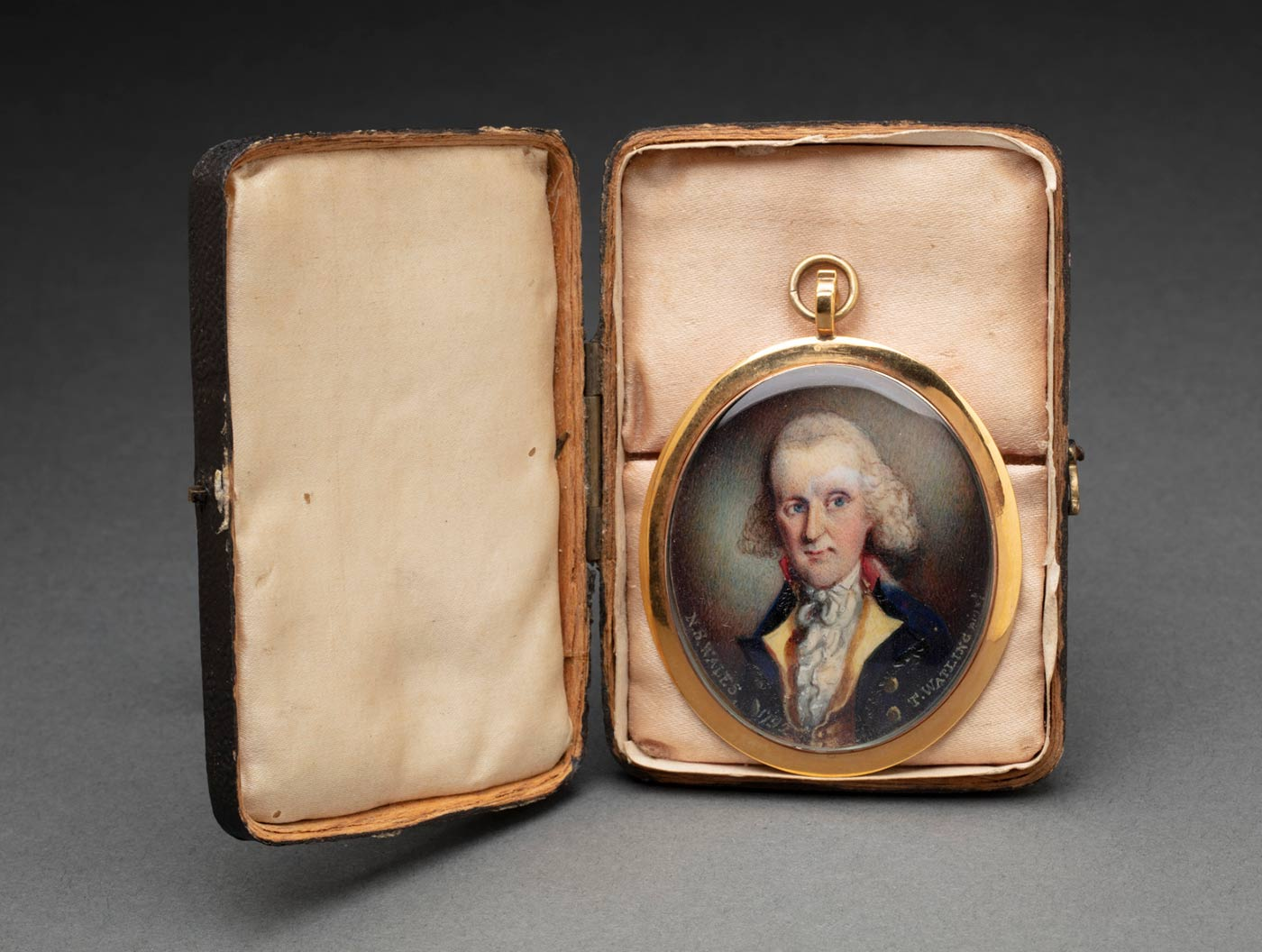 An oval painted portrait depicting a man with white hair wearing a blue coat over a gold vest and a white shirt. Written along the bottom edge is 'N.S. WALES 1792 T. WATLING [?]'. The portrait is mounted in a gold frame and covered in glass. There is a loop at the top of the frame attached to which is a ring. The portrait sits inside a black case which is covered in cream fabric on the lid and pink fabric on the base. The padding in the base is in two sections.