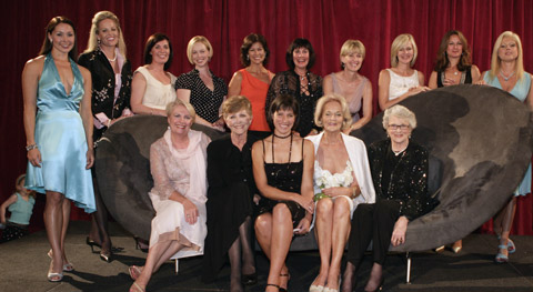 A group shot of fourteen Miss Australia titleholders. Ten are standing in the back row and four are seated on a couch at the front with Sophie Jensen in the centre.