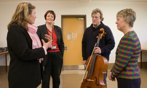 A man holding a cello stands talking to three women.