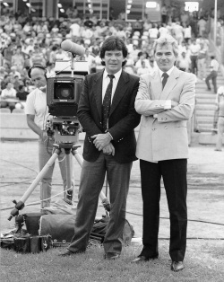 Black and white photograph showing two men standing beside a television camera on a grass field. Both men are wearing suit coats and ties and are crossing their arms. In the background a man wearing a headset uses the camera and there is a crowd of people in tiered seating.